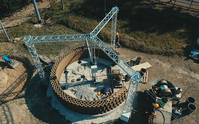 後述で登場する3Dプリンターハウス「GAIA」。3Dプリンターが得意とする曲線を描いたこの家は、巨大なクレーンを現地に設置して素材を積み上げてつくられている(©WASP)