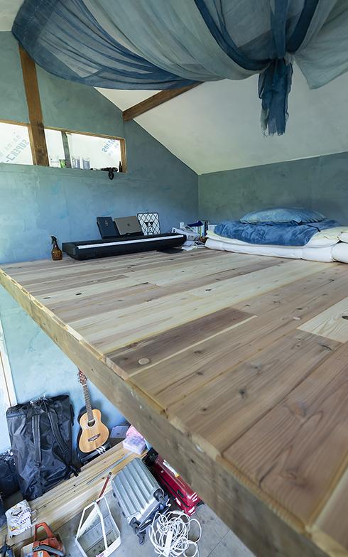 壁には噴火湾産のホタテの貝殻を原料にした塗り壁材「ホタテ漆喰」を使用。虫よけに天井から下げた藍色の蚊帳がブルーの壁に似合っている(写真撮影/川村一之)