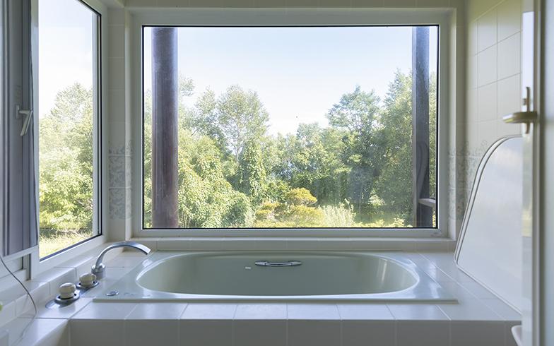 二面に窓を設けたビューバス。湯船につかって畑や庭を眺められるこの家の自慢(写真撮影/川村一之)