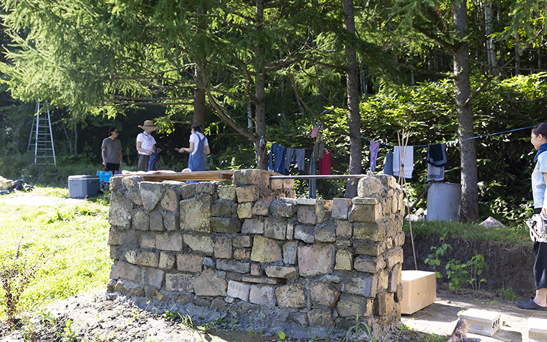 小屋の前につくった石積みのガーデンキッチンはイベントでも大活躍。作業しているとご近所さんが「食べきれないから」と、庭のとれたて野菜や海の幸を届けてくれるそう(写真撮影/川村一之)