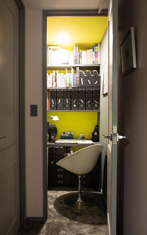 扉の向こうはイエローグリーンの壁に、PCデスクとチェアがセットされた書斎(写真撮影/片山貴博)