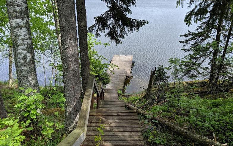 """サウナ小屋の先には階段があり、下りた先は湖。桟橋は、ときに""""飛び込み台""""になり、腰を掛けて足先を水につけて読書するときの""""椅子""""になります(写真撮影/SUUMOジャーナル編集部)"""