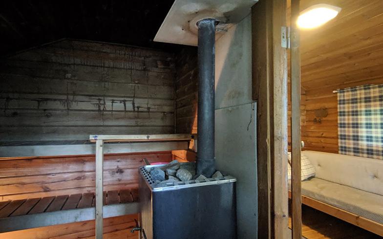 サウナ小屋の内部の様子。オレンジのバケツに湖から取ってきた水を入れておきます。サウナの外に着替えや仮眠ができる小部屋があります(写真撮影/SUUMOジャーナル編集部)