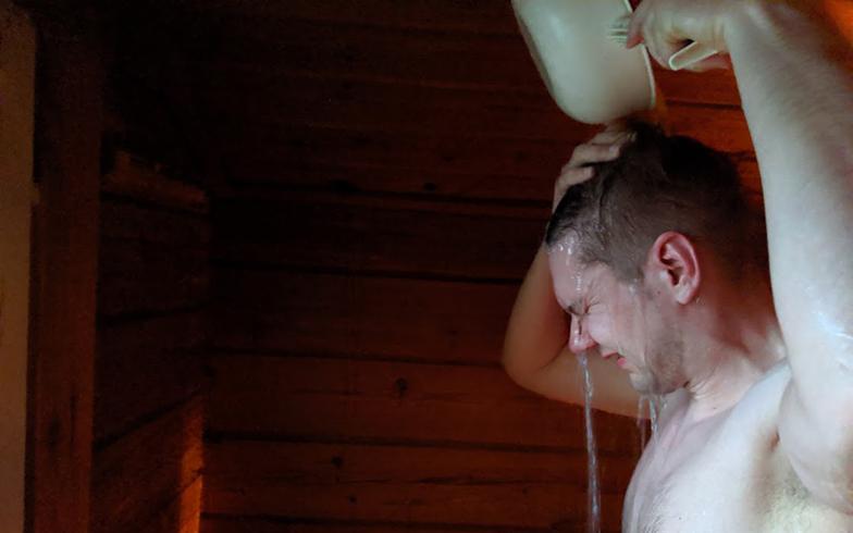 湖で汲んできた水をサウナ用の薪で熱湯に変えて、水を混ぜて適温にして豪快に頭からかぶる。よく見ると少し小枝が浮いているが、そんな小さなことは気にしない様子(写真撮影/SUUMOジャーナル編集部)