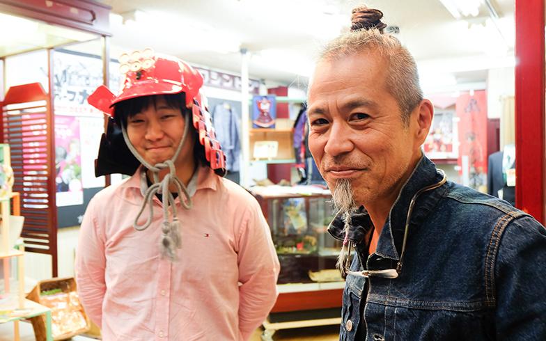 西成区のアンテナショップを営むちょんまげ頭の上村俊文さん。鎧をかぶるのはグラフィックデザイナーの吉村将治さん(写真撮影/吉村智樹)