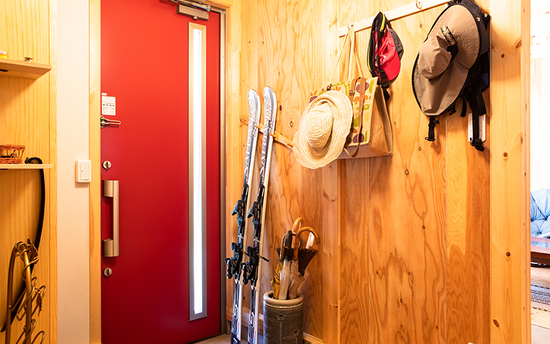赤いドアがアクセントの玄関。既製品のハンガーフックを斜めにつけて、スキー板置き場にDIY (写真撮影/片山貴博)