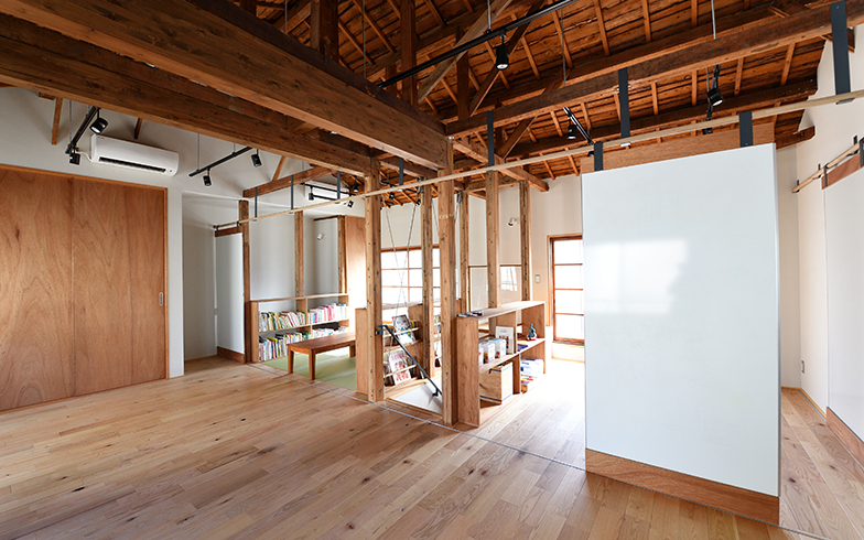 2階のコミュニティスペース。ホワイトボードの間仕切りで部屋を分けることも。奥には子どもが本を読める畳の図書スペース。天井の梁などは改築前の長屋をそのままに耐震補強を加えつつ活用した(写真/水野浩志)