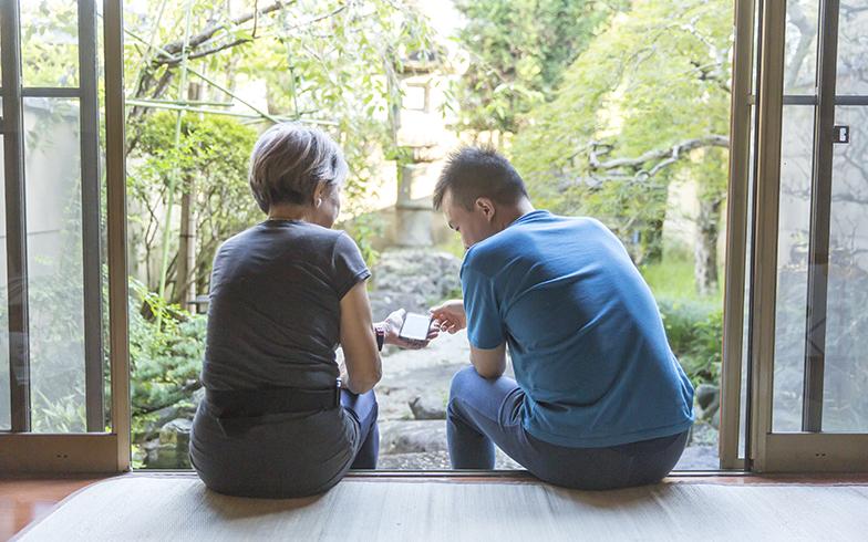 昭和45年に建てられた京都の趣のある住まいを15年前に購入したYさん。縁側に腰掛けて美しい日本庭園を谷口くんと一緒に眺める(写真撮影/中島光行)