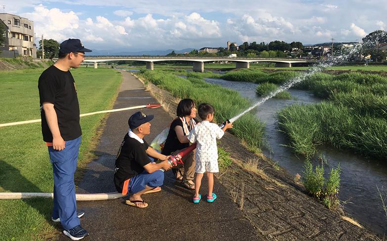 町内会のイベントの様子。自宅の近所に流れる犀川で消防車の放水体験(写真提供/須田麻佑子さん)