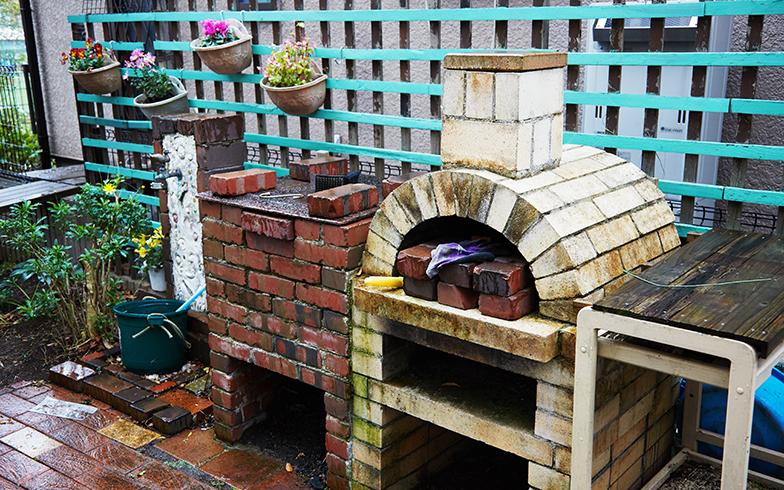 なんと!立派なピザ窯も手づくり。レンガを積んで本格的。水道栓までつくり付け、余った木材で緑のラティスもつくってしまった角方さん(写真撮影/相馬ミナ)