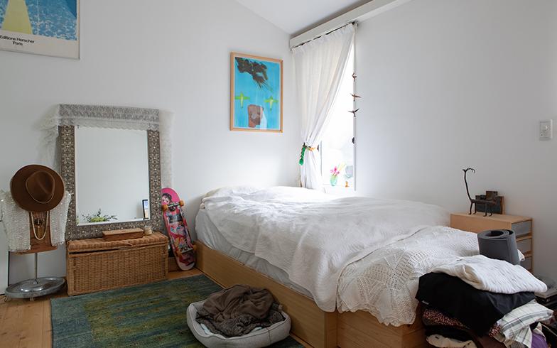 ワークスペースの反対にはベッド。壁にはデイヴィッド・ホックニー(画面左上)などのアートをギャラリーのように飾っている(写真撮影/片山貴博)