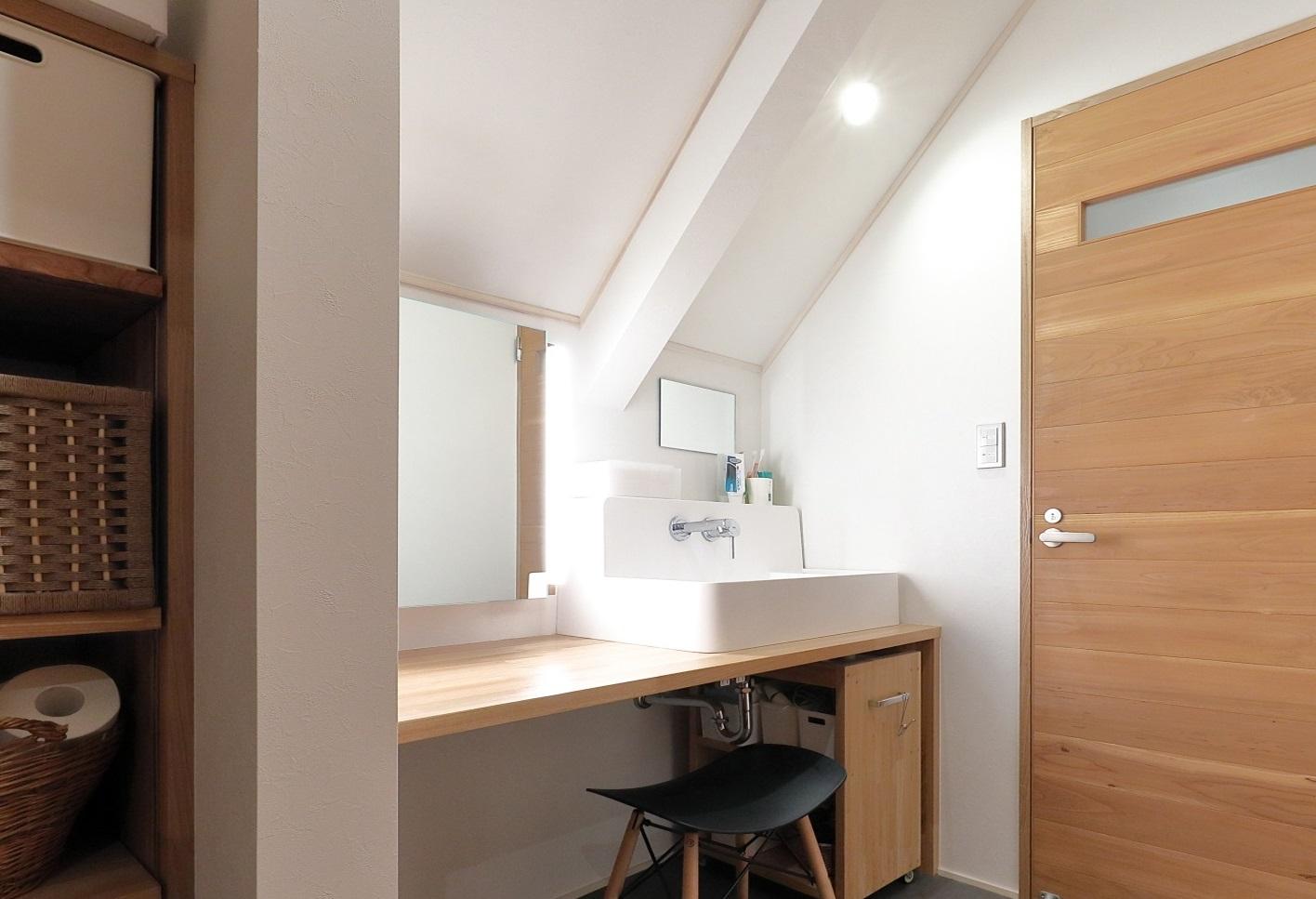 2階のパウダールーム。塗り壁や大工と建具職人がつくった特注の家具や建具など、自然素材の内装材の効果で、あたたかい雰囲気の明るい空間となっている(撮影/筒井岳彦)