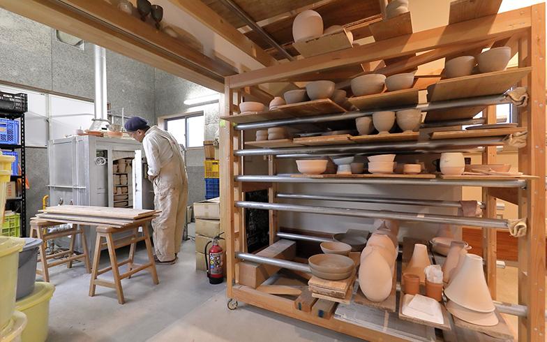 奥にあるのが窯。手前の棚には、成形された作品が、窯で焼かれるのを待っている(撮影/筒井岳彦)