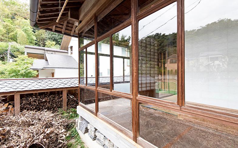 一目惚れした縁側は、一本レールに波打つレトロなガラスの木製建具11枚が並ぶ繊細なつくりをそのままに再現。庭の脇には薪ストーブ用の薪を収納する薪小屋を新設。薪小屋の屋根は今では希少な天然スレート瓦。「薪小屋には贅沢なようですが、室内からも外からも目につく場所なので」と小泉さん(写真撮影/高木 真)