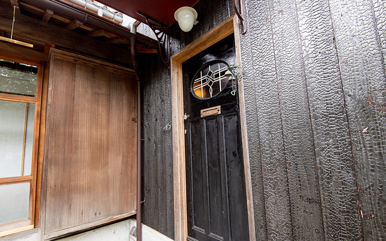 蔵部分に設けられた玄関の扉は1920-30代イギリスのアンティーク。漆喰の白壁とのコントラストが美しい黒の外壁は焼き杉で、伝統を重んじつつ個性を演出(写真撮影/高木 真)