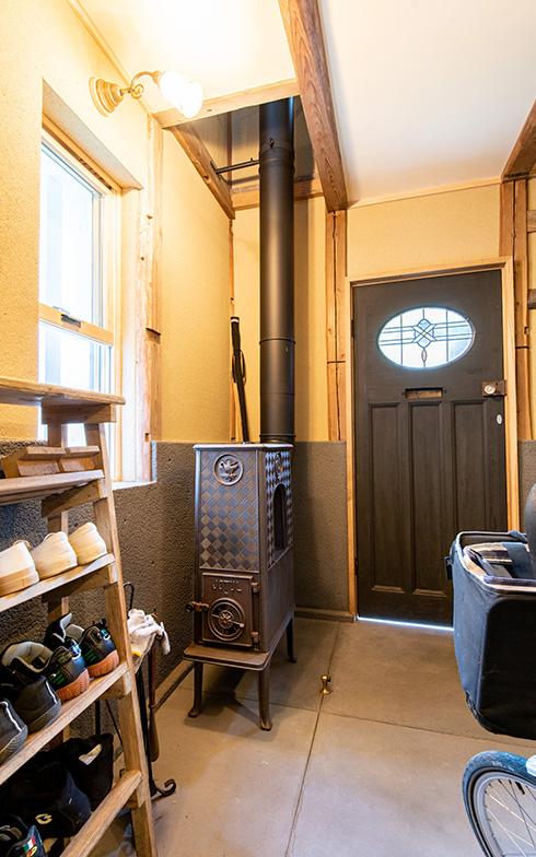 玄関を入ると、1960年代ノルウエーの薪ストーブがある広い土間スペース。薪ストーブは土壁と相性の良い輻射熱式の全館暖房をと考え導入、2階の寝室まで吹抜けになっていて、生活空間である蔵スペース全体がこれひとつで温まる仕組みだ(写真撮影/高木 真)