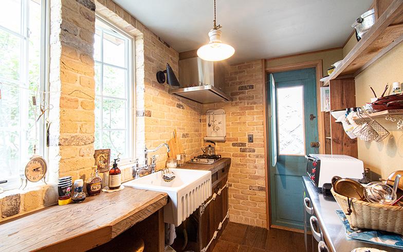 蔵の1階は水まわりなどの生活スペース。イギリスやフランスの片田舎を思わせるキッチン、インテリアのポイントはブルーの勝手口ドア。これもフランスのアンティークで、実はこの家で一番高価だったという(約30万円)。キッチンはこのドアありきで設計が決まったそう(写真撮影/高木 真)