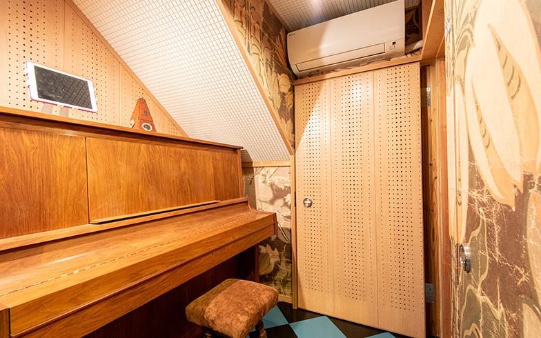 玄関ホールからキッチンに通じる廊下も兼ねたスペースは、両側の防音仕様の扉を閉めると、ピアノ演奏のための防音室になる構造。壁紙はオランダのデザイナーもの、床タイルは市松模様にして機能性を追求する中にも遊び心が(写真撮影/高木 真)