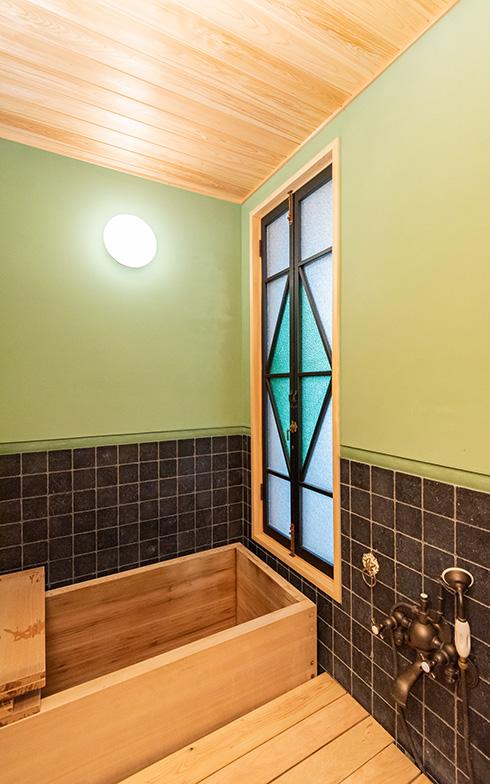 なんともレトロな雰囲気のお風呂。椹(さわら)の浴槽に大正時代のアンティークのステンドグラス、壁はなんと漆喰塗り。水栓金具はテイストが合うものを求めて、フランスの現代ものエルボ社に(写真撮影/高木 真)