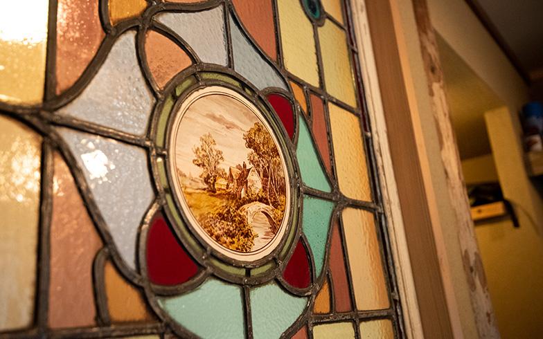 トイレの床タイルも市松模様、便器はアメリカのコーラー社、手洗いにはフランスの陶器のガーデン用シンクを選んでレトロな雰囲気に。ポイントはアンティ-クのステンドグラスで、1920-30年代イギリスのロンデルガラス入り。トイレ側、玄関側、内外どちらから見ても美しい(写真撮影/高木 真)