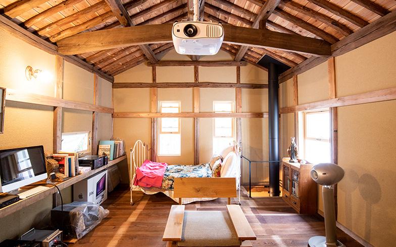 勾配天井を活かした2階の大空間。築100年以上の木材がダイナミックに組み合わされた姿は眺めていて見飽きない。1階にある薪ストーブの配管が吹抜けになって、2階のこの大空間も温まる仕掛けだ(写真撮影/高木 真)