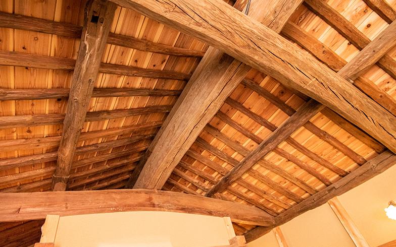 小泉邸の蔵の2階は構造材を全てそのまま見せるデザインの勾配天井にして、更に中央の白い漆喰壁を大画面としてプロジェクター投影ができる大空間。「元々の蔵は倉庫のため、窓も少なく天井も低めのつくり。蔵を快適な生活空間にするため、元の構造材に60センチ分足して天井を高くしたり窓も増やすなどの設計上の工夫をしています」と建築家の大沢さん(写真撮影/高木 真)