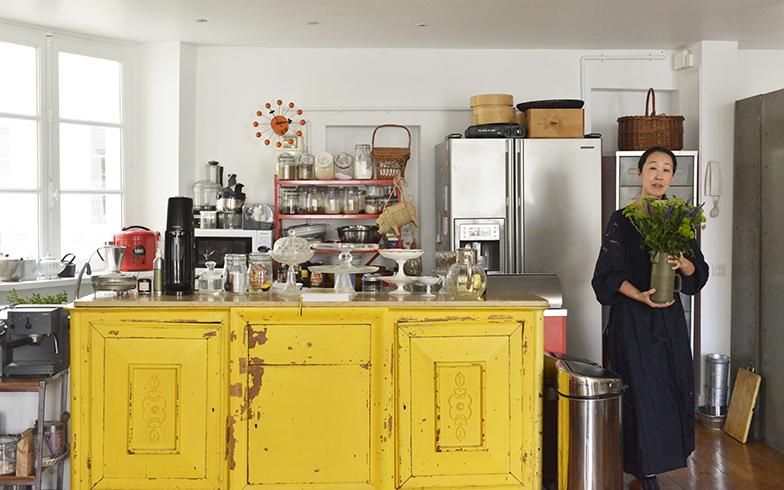 28年前に5000円ぐらいで買った黄色いビュッフェでキッチンとダイニングコーナーを仕切っています。この裏が流し台調理台になっている。花を活けることが好きで、たくさんの花瓶を持っている紀子さん。特に一輪挿しが好きで、気に入ったものがあれば買ってしまうほど(写真撮影/Manabu Matsunaga)