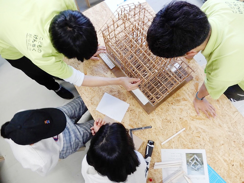 2019年の定期授業(中学生クラス)で、大学生である担任の先生から、日本の木造建築の多くを占める在来軸組の仕組みに関して学ぶ子どもたち(写真提供/こどものけんちくがっこう)