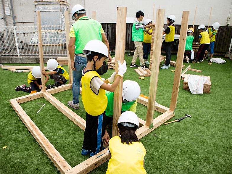 2017年の夏期特別授業で、鹿児島市内の商業施設「マルヤガーデンズ」の屋上「ソラニワ」に、子どもの遊び場「ソラニワモッキ」を建設。大人はボランティアで、サポートに入る工務店も「子どもたちに建築を教えることは、ビジネス抜きで重要」と考えているそう(写真提供/こどものけんちくがっこう)