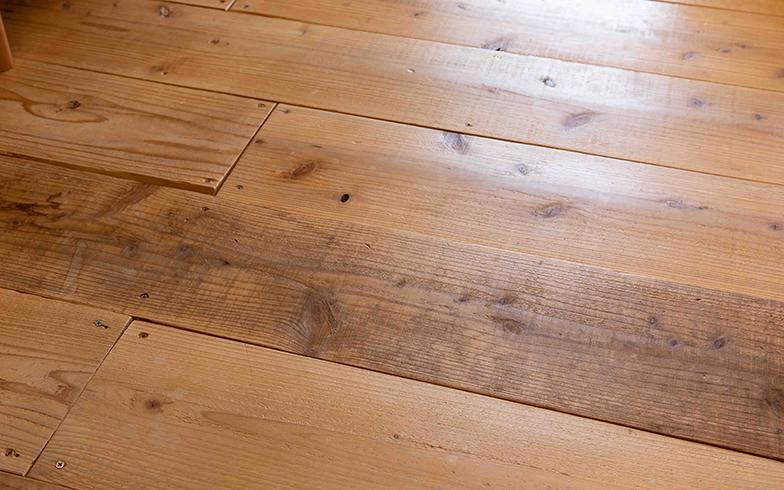 サンダーで表面を削り、ワックスを塗ったリビングの床。自然なツヤが美しい。木の表面のささくれがなくなり、裸足で歩けるようになった(写真撮影/片山貴博)