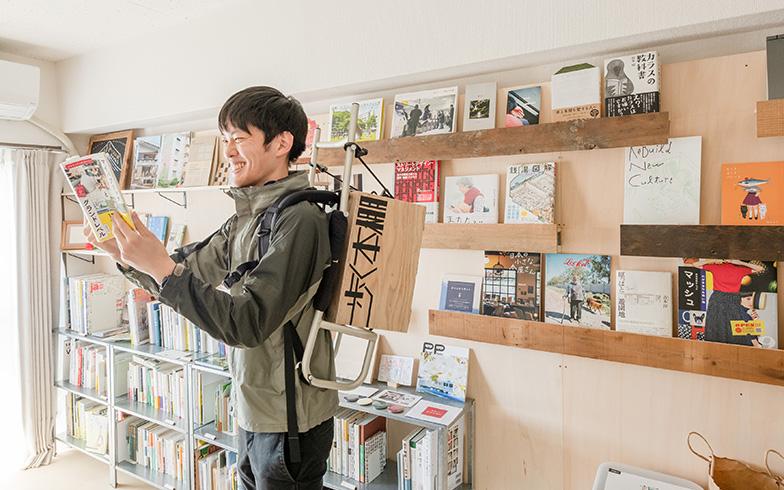 屋外でも図書館を開けるようにと自作したリュック型の本棚を背負って。入居して初めてDIYした作品でもあり、住民に手伝ってもらいながら完成させたとか(写真撮影/田村写真店)