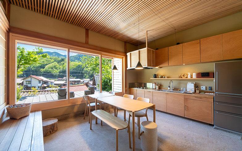 のれんをくぐって建物の中に入ると、広い土間にキッチンとダイニングテーブル。大きな窓の向こうには、のどかな村の風景が広がる(写真撮影/福角智江)