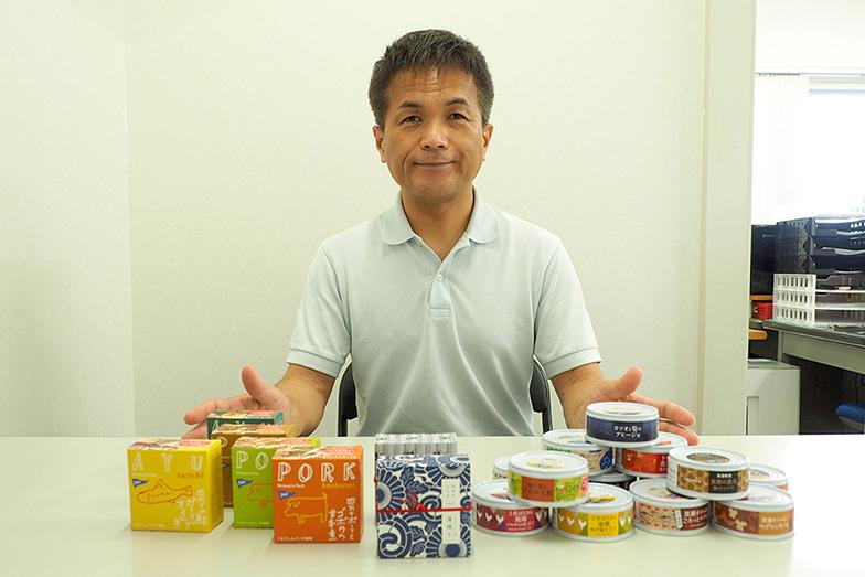商品の缶詰を前にする友永さん。現在は黒糖など地元特産品を使ったスイーツの缶詰にも取り組む(写真/藤川満)