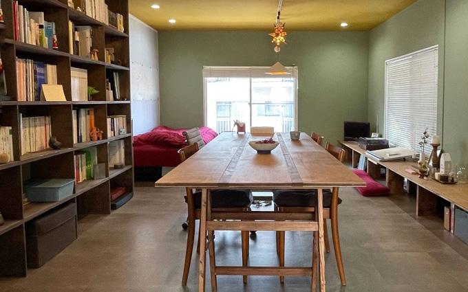 もとは施工会社の事務所だった2階の手前の部屋に自作の家具を配し、落ち着いた雰囲気のリビングダイニングに。既存の壁面収納は本棚として活用(写真提供/「商い暮らし」)