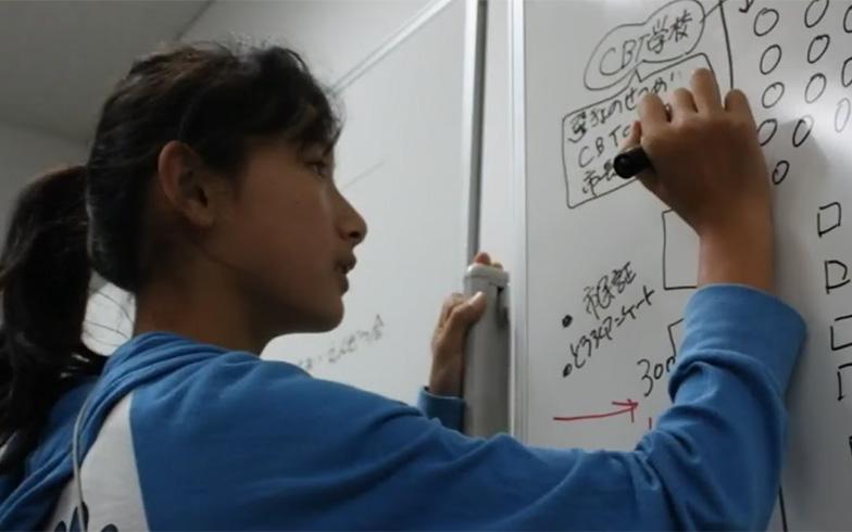 高学年の参加者が、低学年をリードする。会場の配置計画をボードに描いて動線を確認。会場の配置計画や設営など、活動の最初から子どもたちが参加している(画像提供/こどものまちCBT)