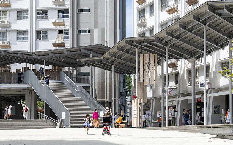"""洋光台駅前すぐの高層棟・洋光台中央団地に新設されたアーケード屋根。中央広場を囲むようにぐるりと設置されています。ゆるりと居場所をつくるさまは、まちの""""縁側""""です(写真撮影/桑田瑞穂)"""