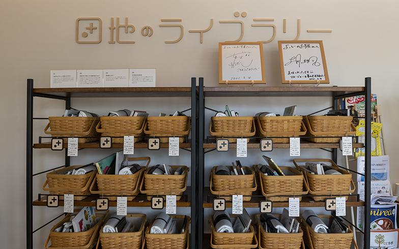 「団地のカフェ」内にある「団地のライブラリー」。監修はブックディレクターの幅允孝氏。本とレジャーシートをバスケットに入れて本棚に並べたもので、団地住民でなくても利用できる「開かれた場所」です(写真撮影/桑田瑞穂)