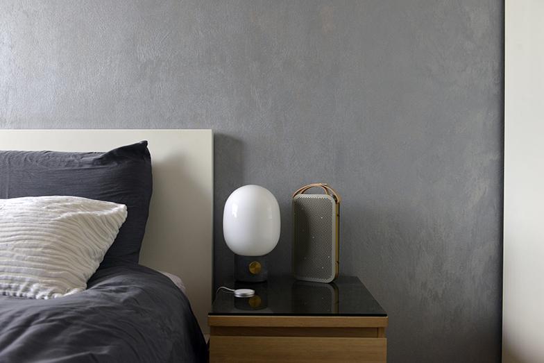 ベッドサイドテーブルには、デザイナーもののランプとB&Oスピーカーがあり、夜寝る前に音楽を聴きながら読書をするのが日課だそう(写真撮影/Manabu Matsunaga)