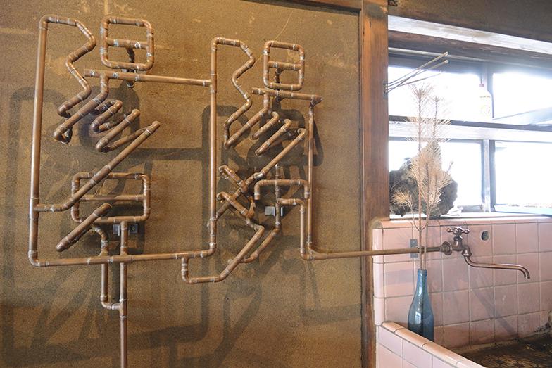 """家屋の構造上、水道の配管が露出されること、昔の銅管の質感のよさに着目し、配管で文字を描いたアート作品を制作。「配管工がさながら伝統工芸士になり、その場を感じてこうした作品をつくったらいいなと思い、手がけました。""""配管グラフィティ""""と名づけています」(写真撮影/内海明啓)"""