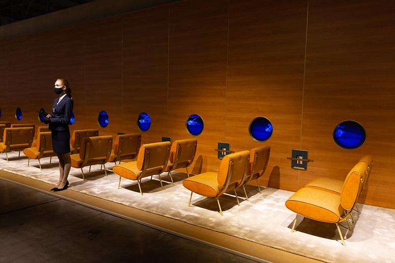 Molteni&C社:飛行機内のような展示で、アテンダントの女性が「アテンションプリーズ」とアナウンス、窓の外には雲の合間に家具プロダクトが浮かんで流れる映像が流れている。座席は1954年に巨匠ジオ・ポンティによってデザインされたアームチェアの復刻デザインの新作「Round D.154.5」。自由に旅できる日が待ち遠しいと思わせるような、ロン・ジラッドらしいウィットに富んだインスタレーション(画像提供/Diego Ravier by Salone del Mobile.Milano)