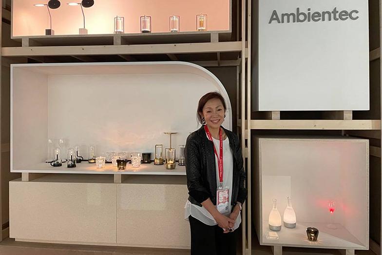 ミラノサローネ広報山本幸さん、日本から初出展のポータブル照明ブランドAmbientec社の前で (画像提供/山本幸)