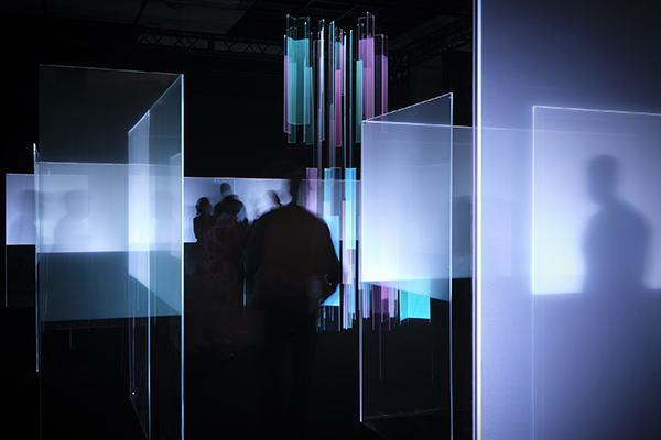 クリエイションパートナーは面出薫(建築照明デザイナー)。透明な「RAYCREA(レイクレア)」フィルムをガラスやアクリル板に貼り光源を組み合わせることで、フィルムを貼った面だけが光る。光の迷宮のような会場(画像提供/Nitto)