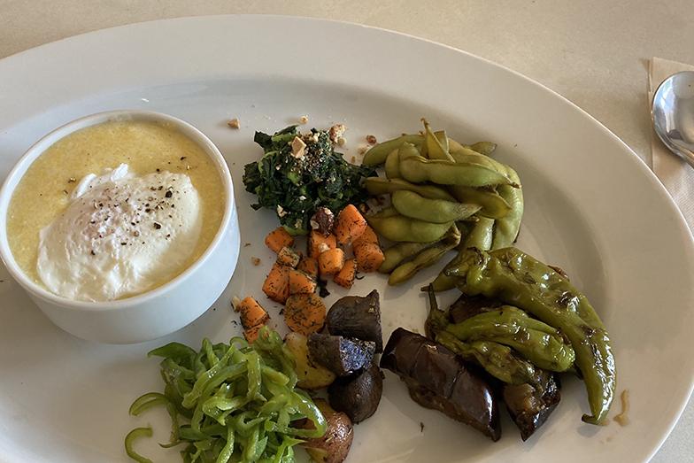 定番メニューはグリッツという、トウモロコシの粉でつくる、卵の入ったおかゆのような料理。滋味深く優しい味で美味しい。そのほか食べごたえのある野菜のおかずで満足感がある(写真撮影/甲斐かおり)